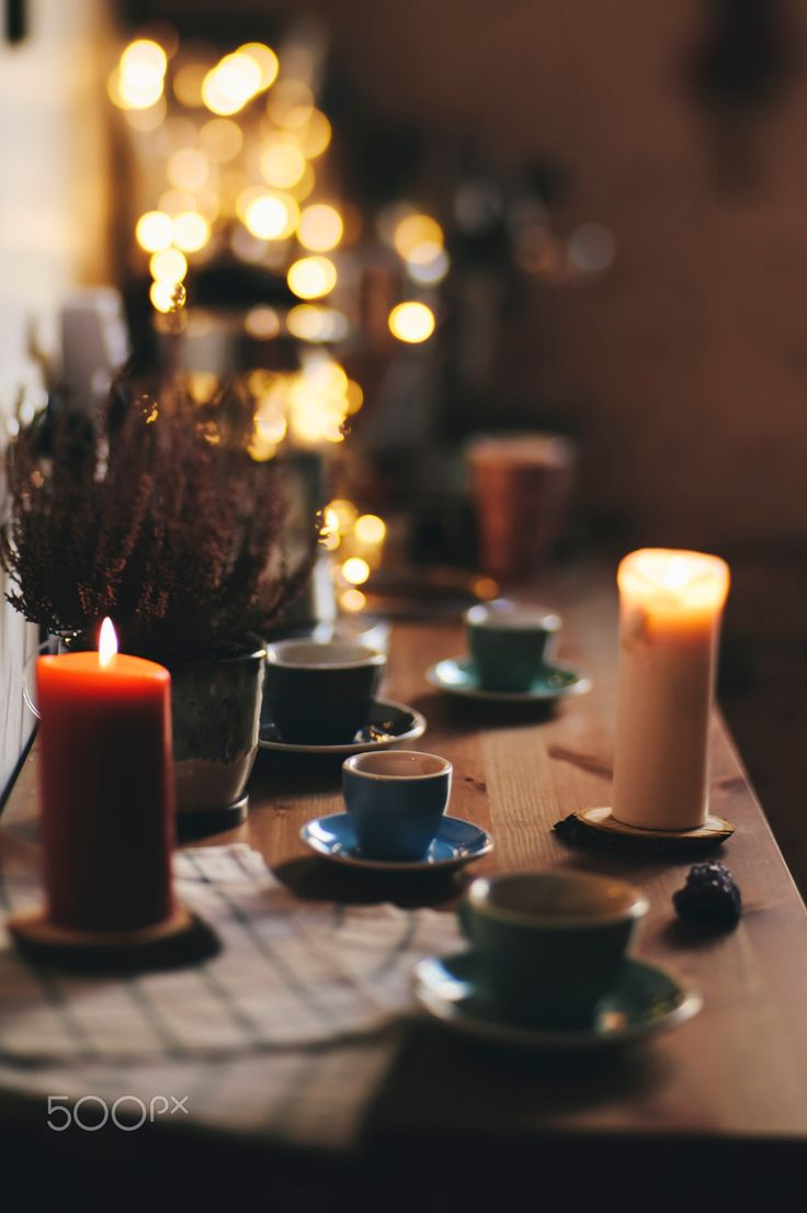 Festive table - Festive dinner wooden table. Nice cups with saucers, christmas fireflies, some burning candles