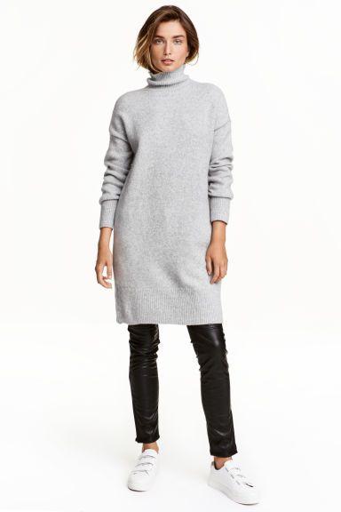 Lange coltrui: Een lange, gebreide coltrui van zachte kwaliteit met wol. De trui heeft verlaagde schoudernaden en een brede, ribgebreide boord aan de onderkant en onder aan de mouwen.