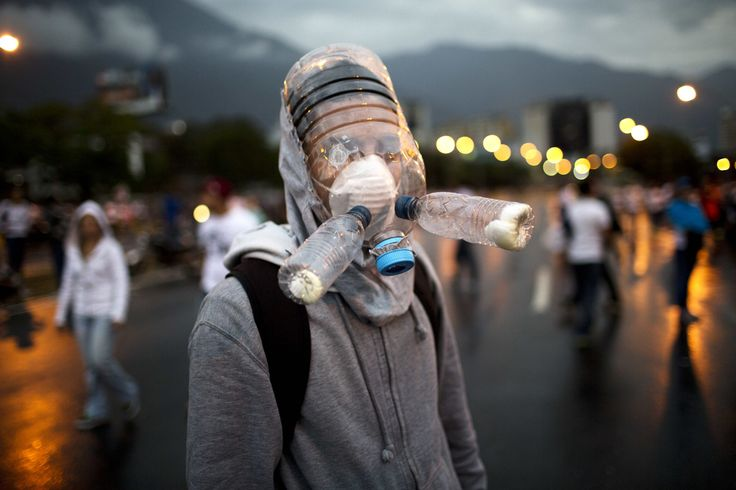 A protester wearing a gas mask made from plastic water bottles, during an opposition protest blocking a highway outside La Carlota airport in Caracas, on February 18, 2014. (AP Photo/Rodrigo Abd)