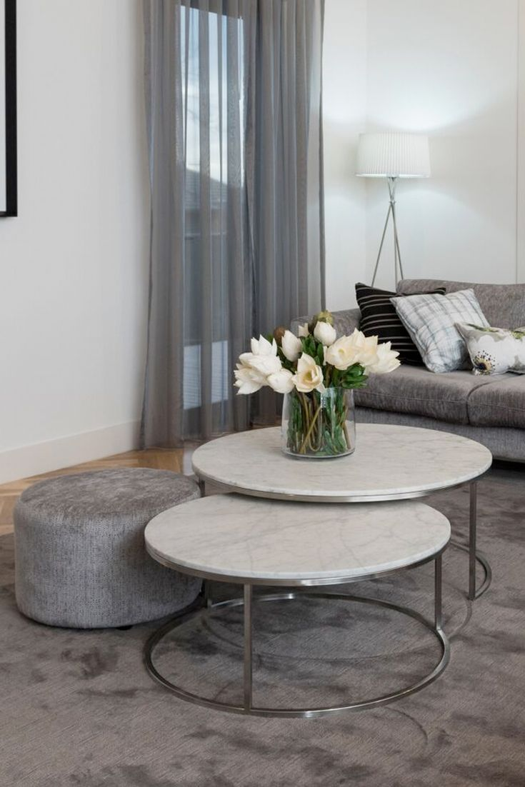Living room design featuring a set of marble nest of tables with a custom upholstered ottoman in silver grey tones.