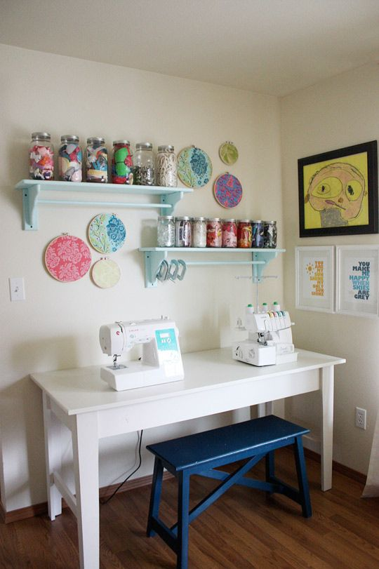 What  a great sewing station!  Love that she used embroidery circles (or whatever you call them) to stretch fabric and add some art to the wall......ideas!  And I also love the shelves and the kids art work - what the heck - I Love it all  :)