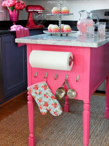 For extra serving and prep space, a custom island made from an old console table was updated with a spray-coat of bubble-gum pink lacquer. It was then outfitted with hooks for kitchen supplies and topped with a Carrara marble remnant.