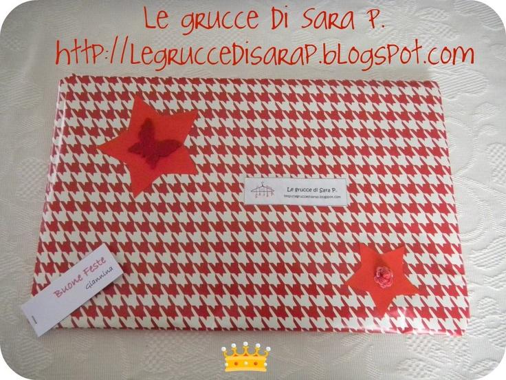 Pacco regalo con carta piedipull, stelline di cartoncino rosso e una farfallina rossa in pannolenci
