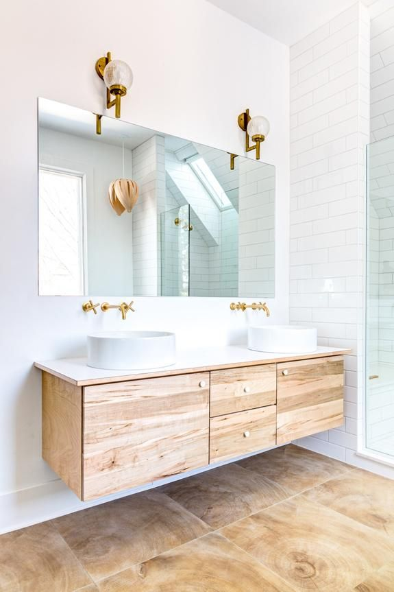 Floating unfinished wood credenza and cabinets underneath double basin sinks with wall-mounted brass sink faucets and fixtures, brass orb wall sconces above the vanity mirror and white floor to ceiling subway tiles with white grout.