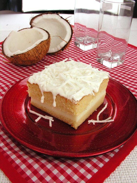 Na foto, um pedaço do bolo gelado de coco está em um prato de vidro vermelho. O bolo tem duas camadas de massa, cobertura e recheio cremoso. Na decoração ao fundo estão dois copos e um coco quebrado.