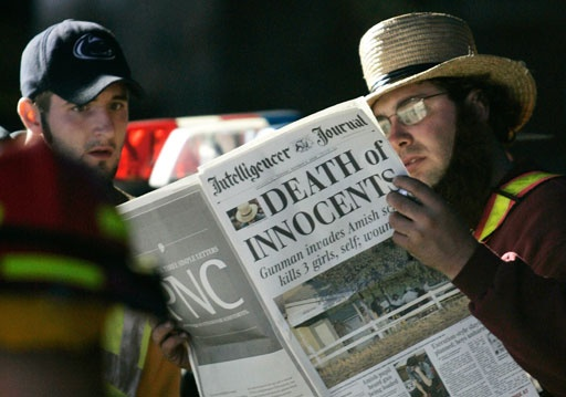 "Two men read a newspaper with the headline ""Death of Innocents"" while standing at a roadblock near the scene of the shooting at the one-room Amish schoolhouse Tuesday, Oct. 3, 2006 in Nickel Mines, Pa. Officials said a milk truck driver identified as Charles Carl Roberts IV entered the schoolhouse, let the boys and adults go free, tied up the girls and shot them execution style before committing suicide. Five girls died."