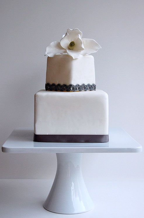 A sugar magnolia flower and grey lace and ribbon details make for a modern and elegant wedding cake.