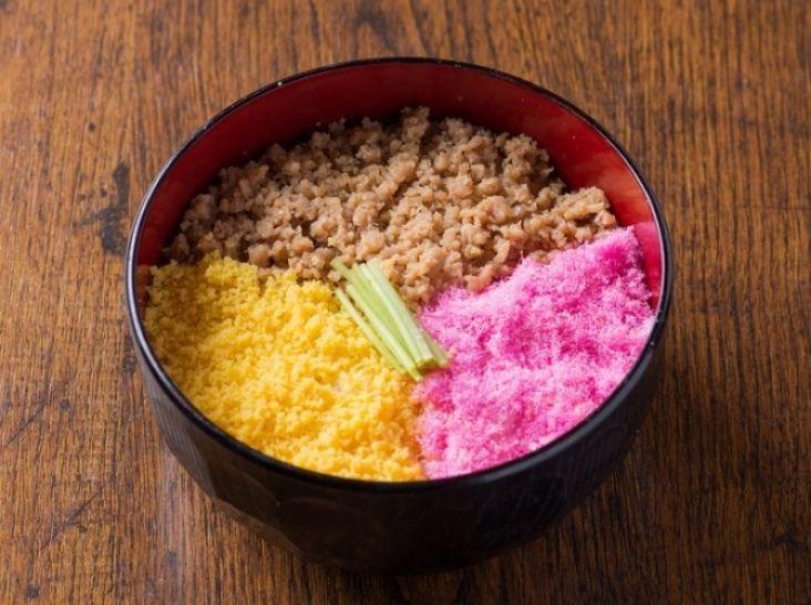 なすひかりの三色丼 - 飯塚 康太シェフのレシピ。鶏そぼろは、火にかける前にお肉と調味料を混ぜておくことで、ポロポロのそぼろになります。 いり卵を作るときは、4~5本の箸を使い、絶えずかき混ぜ続けること。 桜でんぶは、食紅を入れてからよく混ぜることで全体がキレイなピンク色になります。