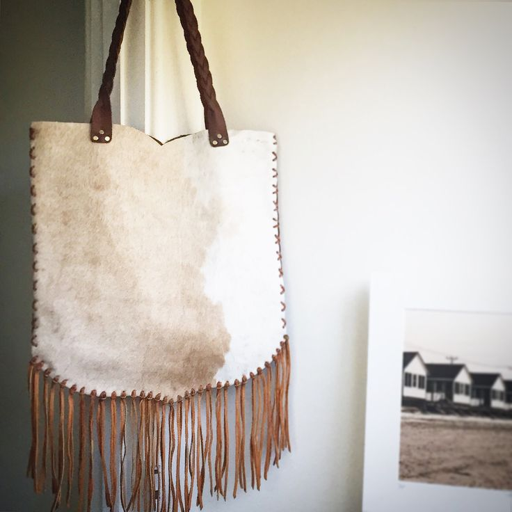 "Rich, beautiful cowhide on one side, rugged saddle leather on the other with our iron-branded label. X-stitched details on sides and back. The softest deerskin fringe and the ""Route 66"" shape make thi"
