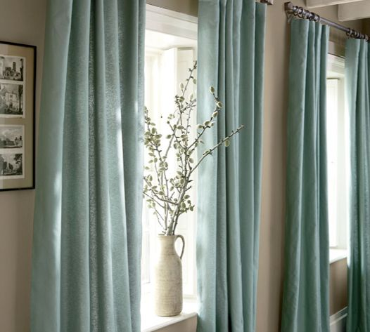 """Para """"agrandar"""" una ventana pequeña, cuelga cortinas por encima del marco que las cubran por completo y lleguen al suelo."""