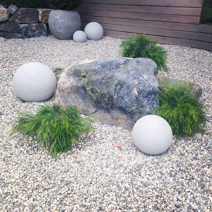 The New Backyard Cottage landscaping - boulder, plants, spherical stones.