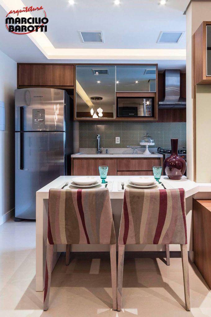 Cozinha pequena integrada a sala com ar moderno utilizando espelhos nas portas dos armários