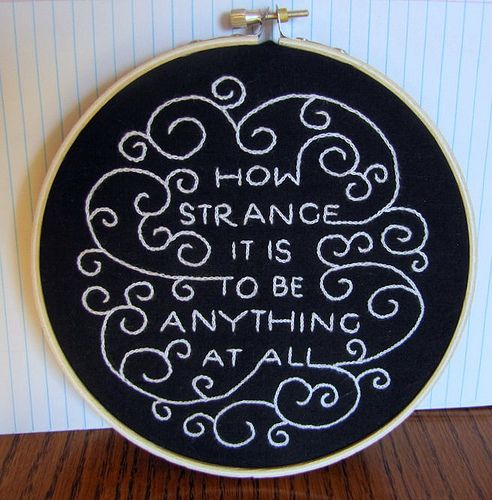 """quote from a Neutral Milk Hotel song, very gorgeously embroidered by Mel. Her embroidery is based on a print by Fionn Breen"". ""This is actually a quote from Alice in Wonderland, by Lewis Carroll.""  i love the swirling.. different quote?"