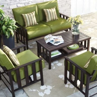 Brighten up an outdoor patio with a statement rug and bright cushions.
