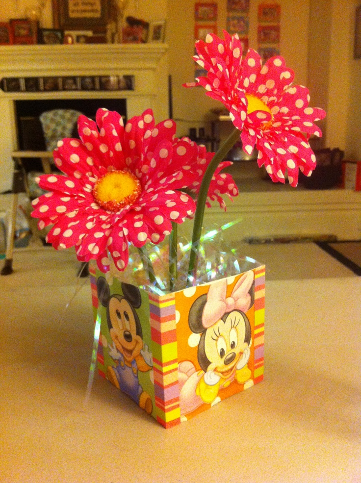 Custom centerpiece. Took a mug box and glued napkins to sides. Trimmed out with scrapbook paper. Foam block inside with polka dotted gerber daisies.