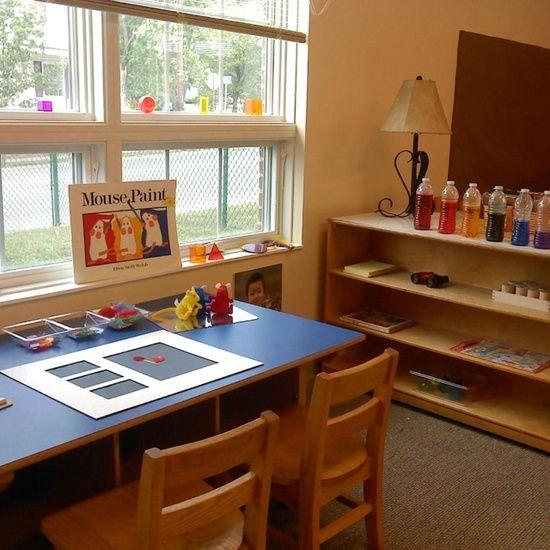 Reggio Emilia classroom. Love the empty frame idea and colored water bottles