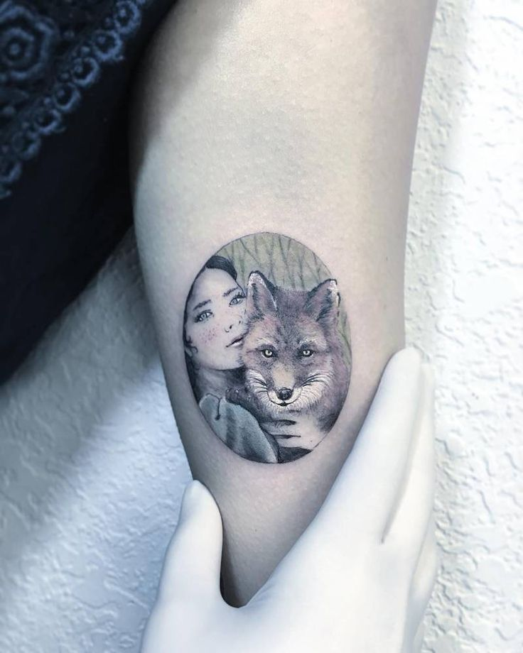 Woman and fox illustrative tattoo on the left inner arm.