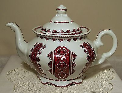 traditional teapot decorated with Ukrainian embroidery patterns in red and black on white body, ceramic, may be from Canada
