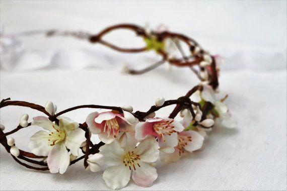 Una corona di fiori molto delicato caratterizzato da fiori di ciliegia bianchi con centri rosa chiaro.  Leggero e completamente regolabile, è molto romantico