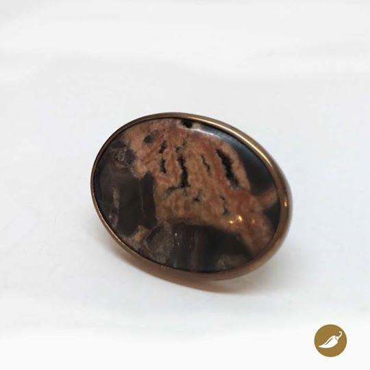 La septaria, caracoles de agua dulce fosilizados, fueron convertidos por MONOCO en una joya. Este poderoso anillo esta engastado en cobre sobre un aro de plata. Sus tonos rojizos son una oda al otoño. Autor:MONOCO Dimensiones: Talla 19,5 cm y la piedra 3,8 cm por 5 cm y altura 0,7 cm Colección: Piedras Materiales: Plata, Cobre y Fósil. Pieza única: Sí.