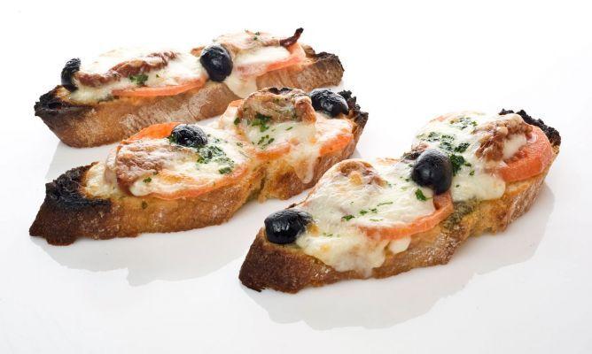 Riquisima tosta de verano realizada por Bruno Oteiza, compuesta de tomate, aceitunas, queso mozzarela y salsa de pesto.