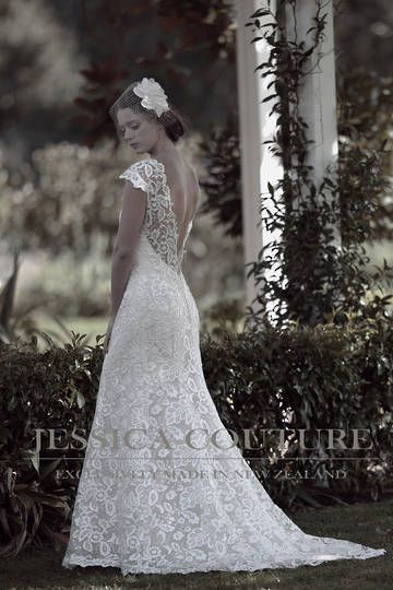 Dress: Claudette.Exclusive laser cut floral pattern lace falls over the body with illusion neckline in a soft fit-n-flare that kicks out into a scalloped hemline with a sweep train. This gown features a very deep open back with capped sleeves design.
