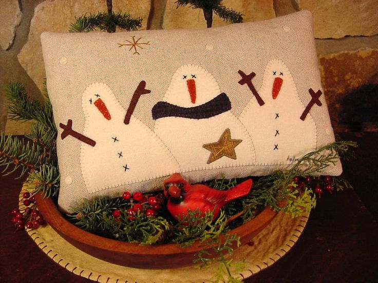 Wool Snowmen Threesome ----  A hand-did primitive pillow for your Holiday decor and to keep out all winter long.  Ive hand cut the snowmen from a felted old wool skirt and appliqued them onto a coarse, reclaimed rustic light ecru linen and added their felted wool accessories, including the dark blue plaid woolen scarf. Then I embroidered their coal eyes and buttons, added falling snowflakes all around and a golden shining star in the sky. The pillow back is an indigo blue & beige plaid b...