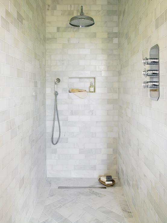 Gorgeous marble walk-in shower is clad in honed marble subway tiles accented with a marble tiled shower niche and a rain shower head over a honed marble herringbone shower floor.