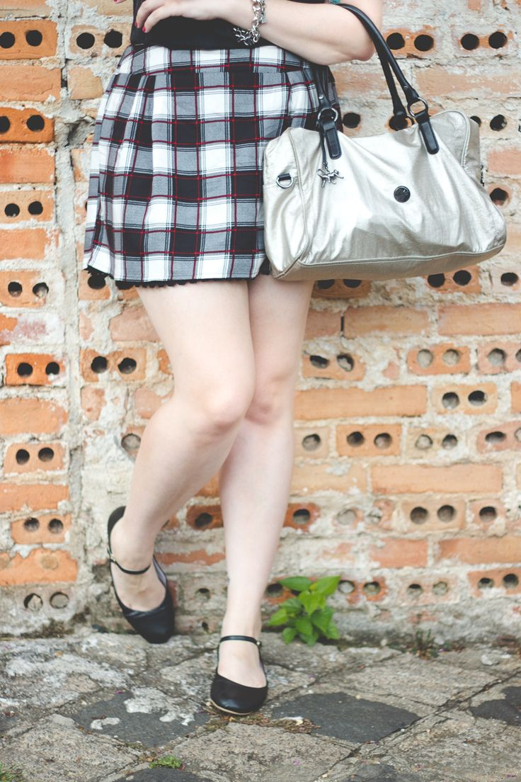 Look com saia xadrez quadriculada regata preta bolsa prateada e sapatilha preta