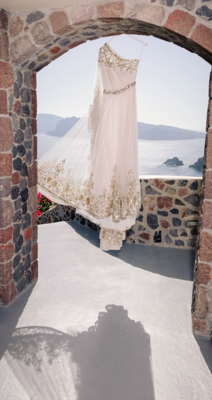 Beautiful Wedding Dress inspired from ancient Greece with breathtaking Santorini view! See more here: http://photographergreece.com/en/photography/wedding-stories/946-vintage-wedding-at-santorini-arts-factory