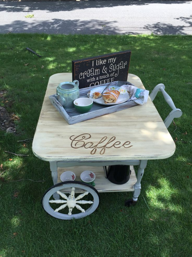 """Sweet tea!!!! Antique tea cart transformed into a tea and coffee/bar!!!! Both sides fold down. Extra pull out tray to Serve your guest. Cream and grey super distressed with a dark wax ! All sealed and smooth---- this vintage cart has awesome large wheels! There is a special Handel that you can pull and Push. 28 1/2 height Lenth 33"""" when sides are up Width 2ft.... SWEET TEA . Is ready to brew your first cup of coffee and enjoy a sweet apple turnover. She is priced for purchase 195.00 (firm)"""
