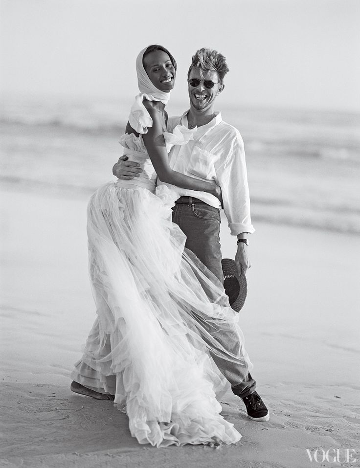 Iman, in a dress by Karl Lagerfeld for Chanel Haute Couture, and David Bowie on the beach at Cape Point Nature Reserve near Cape Town, South Africa.    Photographed by Bruce Weber, Vogue, April 1995