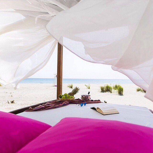 Кровать на пляже, позовые подушки, белые балдахин, море, книга, белое одеяло