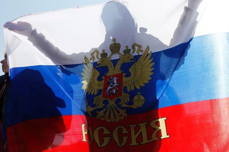 Une femme tient un drapeau russe lors du référendum sur l'indépendance des provinces ukrainiennes de Donetsk et de Lougansk à Simféropol