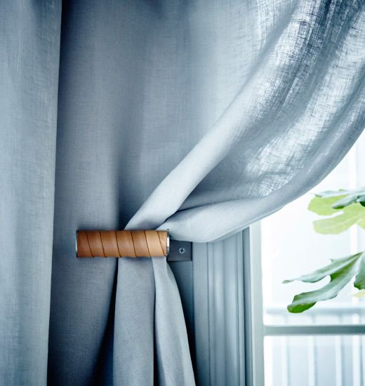 A IKEA GRUNDTAL toilet roll holder is mounted next to window to serves as a curtain tie.