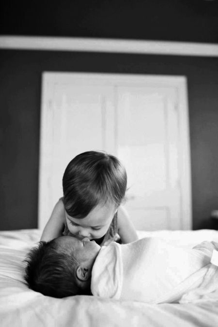 Photos of babies. Sibling photo shoot. Black and white. I could see Emma doing this, she kisses my belly now. :)