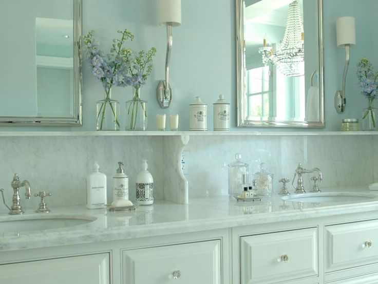 source: Berkley Vallone  Gorgeous bathroom with white dual vanity featuring crystal hardware and his and her sinks with traditional style faucets framed by a marble countertop with backsplash ledge. The vanity pairs with polished nickel mirrors flanked by polished nickel sconces, Ruhlmann Single Sconces in Polished Nickel, over light blue walls.