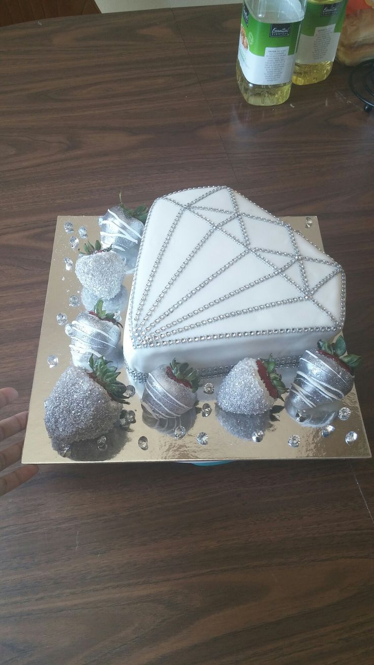 Diamond shaped cake with white chocolate covered strawberries coated with sparkles and glitter.
