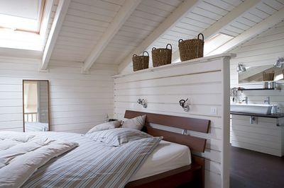 Salle de bains ouverte sur la chambre avec lambris peint en blanc