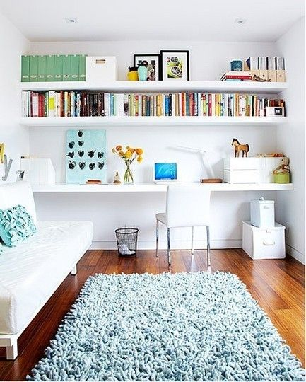 A wall of shelves staggered to provide both ample storage space and a broad work surface is a clean, simple solution that is at home in the living room. Image via Apartment Therapy