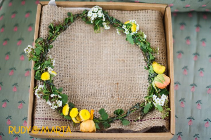 flower crown of bacopa, orange ranunculus, spirea and yellow button chamomile for the flower girl.