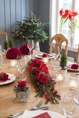 Roser og nelliker sammen med vintergrønt og kongler skaper en hyggelig julestemning.