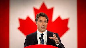 In the photo is a man standing in front of a Canadian flag. The man is Justin Trudeau, who is the current prime minister of Canada. Trudeau is faced with many important issues in Canada such as terrorism, and air pollution which will require him to make many decisions that impact millions of people. Trudeau is part of the Liberal Party of Canada, which has the same values as the Liberal Party of the U.S.