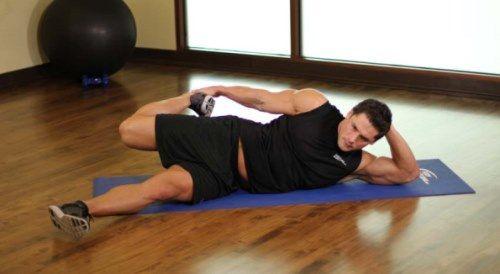 EJEMPLO II: 1. Título: ESTIRAMIENTO DE CUÁDRICEPS.  2. Musculatura implicada: CUÁDRICEPS. 3. Descripción del ejercicio: Tumbado lateralmente sobre el suelo y con la pierna más próxima al mismo totalmente extendida. Se realiza una flexión de rodilla de la otra pierna, llevando el pie hacia el glúteo. El ejercicio puede estar asistido con el propio brazo.