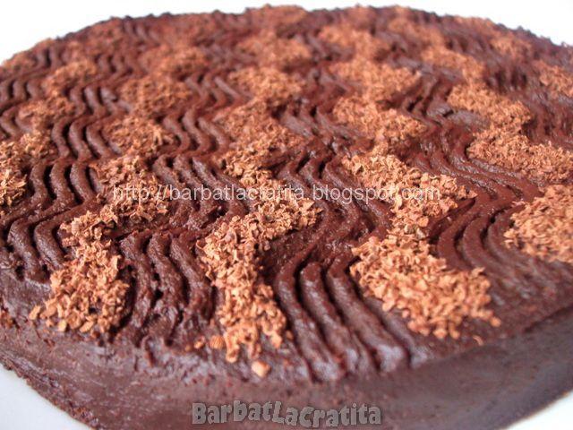 Tort simplu de ciocolata cu blat de cacao imbracat in crema si decorat cu putina ciocolata rasa.