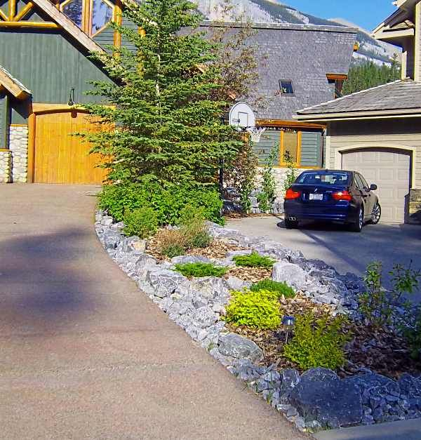 Driveway landscaping between two neighbors with a small for Sloped driveway options