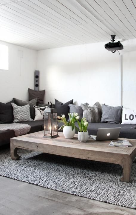 White/grey living room with wooden details. The living room table is gorgeous!