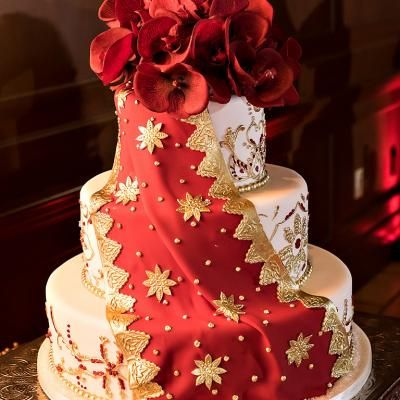 Stunning three teir round wedding cake with gold designs and red fabric made out of gumpaste   SJA Studios   villasiena.cc