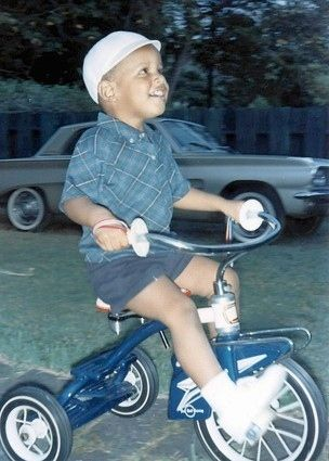 A young future President Barack Obama riding a tricycle.