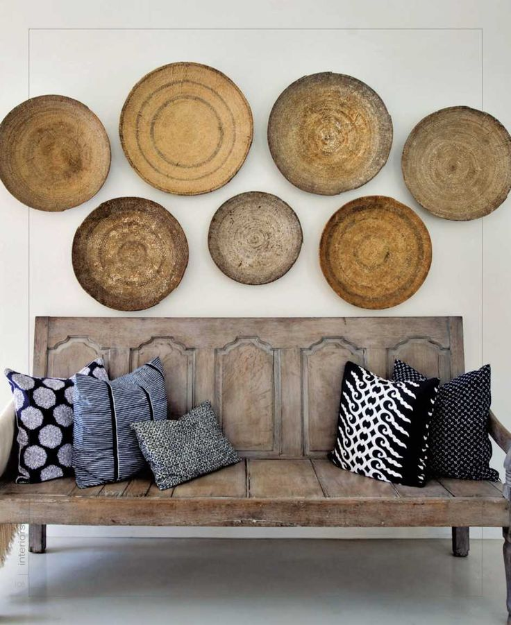 Gorgeous vignette with baskets on wall and bench made from reclaimed wood. Could be built with old cabinet doors.